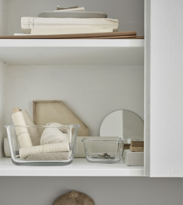 The door of this white storage cabinet is open to reveal small glass containers keeping small items organised.