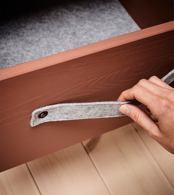 The drawer of a bedside table is lined with grey felt and has a felt handle.