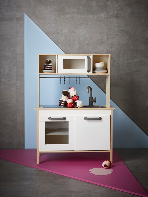The DUKTIG play kitchen in a room with concrete floors, and a blue triangle painted on the wall.