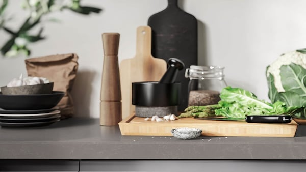 The edge of a gray quartz countertop with a cutting board and other cooking utensils.