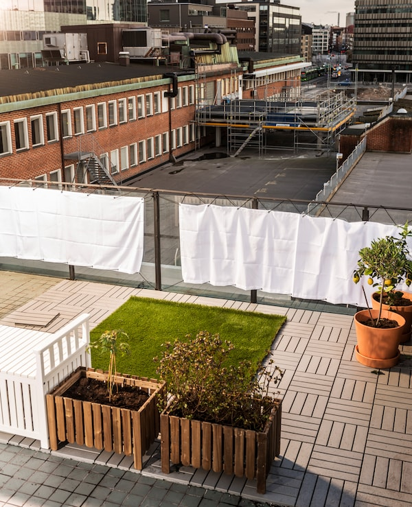 The first elements of the rooftop garden are put into place: windshields, grass, decking and planting boxes.