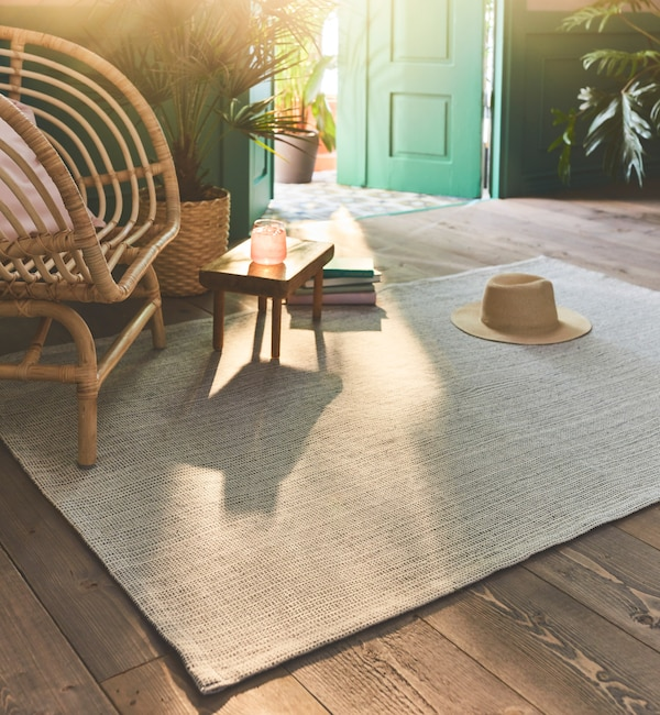 The flatwoven TIPHEDE rug in a natural/off-white color placed on a wooden floor by a wicker chair in a sunny room.