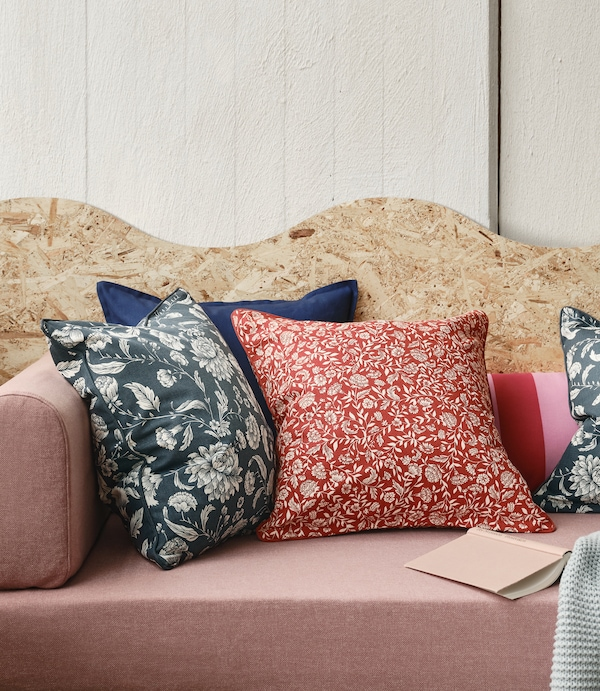 The floral EVALOUISE and IDALINNEA cushion covers are placed in a pink sofa with a plywood structure behind.
