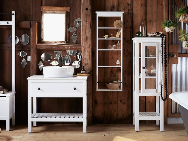 The four white-stained pine storage pieces of HEMNES bathroom furniture series are shown in a wood-panelled rustic bathroom.