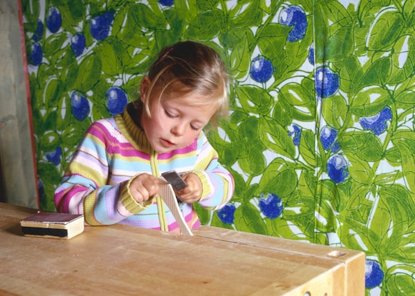 The girl is sanding a piece of wood carefully.