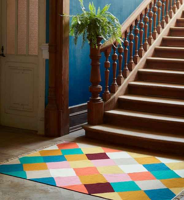 The handwoven VINDERÖD rug in wool made in a colorful, checkered pattern, placed at the bottom of a staircase.