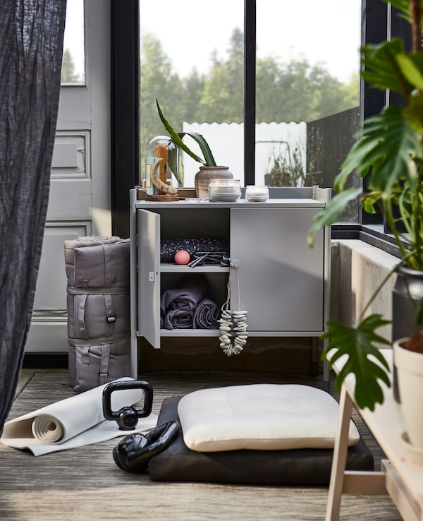 The HINDÖ indoor/outdoor cabinet works as storage space for exercise equipment.
