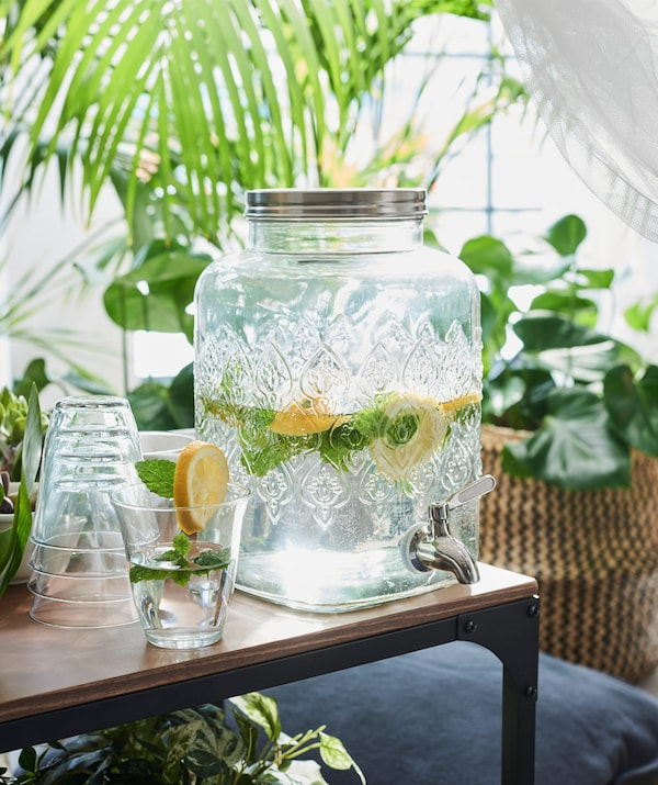 The IKEA FÖRFRISKNING glass beverage dispenser with a tap storing water with mint and lemon on a buffet