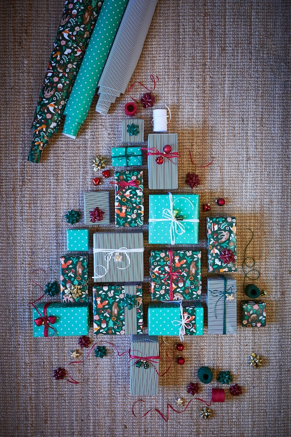 The IKEA VINTER wrapping paper range, lying on a wooden floor in the shape of a christmas tree.