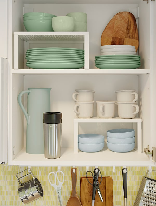 The inside of a cabinet depicted with an array of tableware including mugs, bowls, dishes and more.
