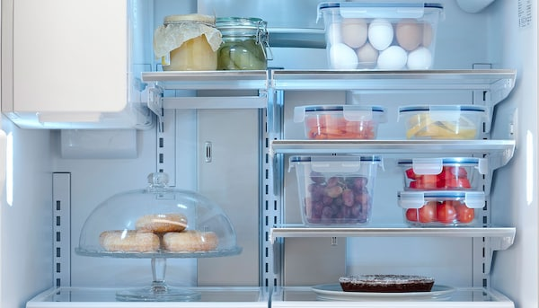 The inside of a STJÄRNSTATUS fridge featuring multiple food storage containers.