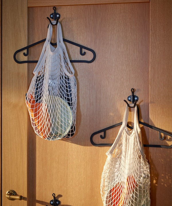 The inside of a wooden front door, fitted with scattered hooks. From each hook hangs a hanger and a net bag with dinner kit.