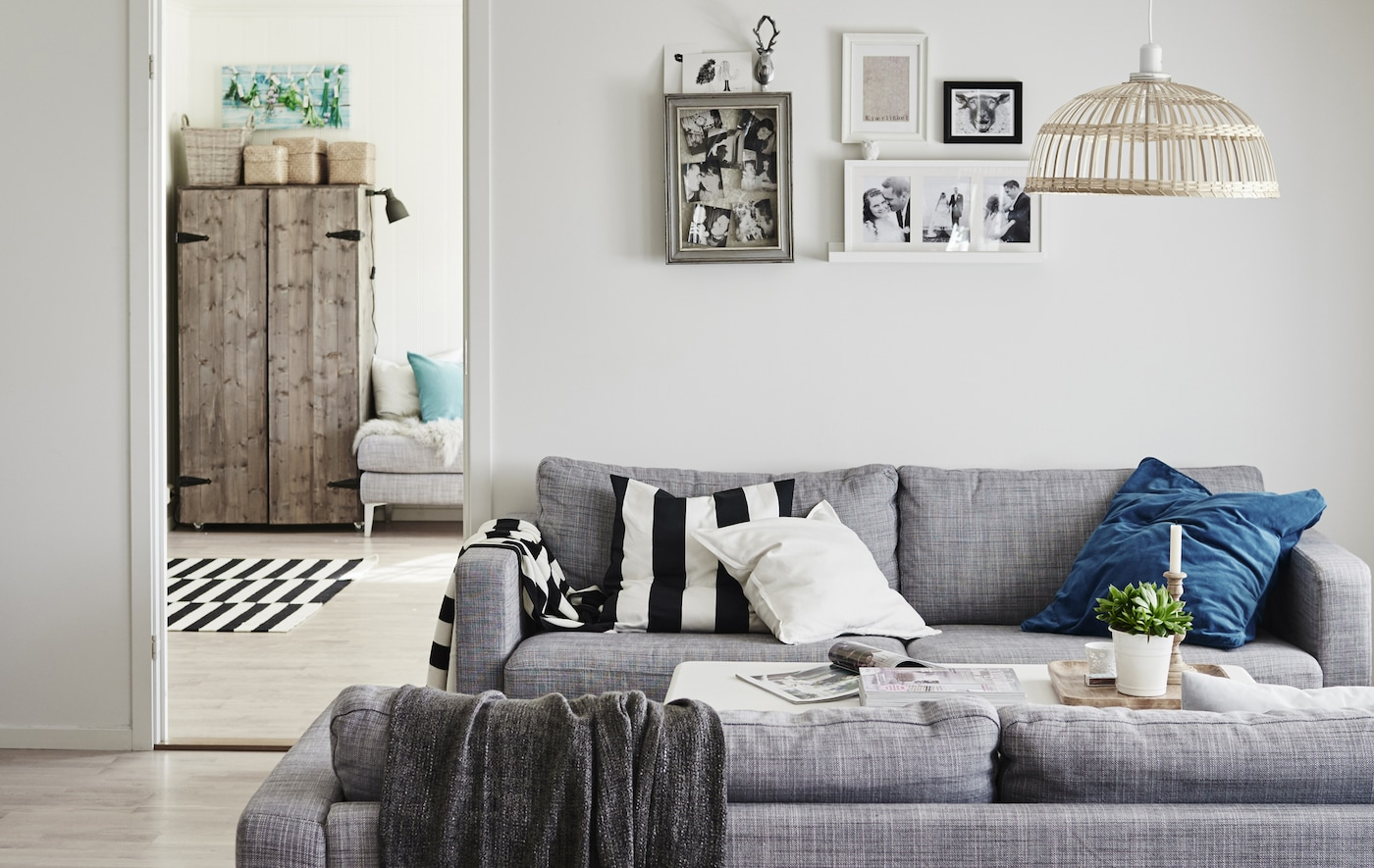 The layout of Gina's living room, which includes two grey sofas facing each other, styled with blue accent cushion colours.
