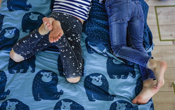 The legs of two boys laying on a bed with blue animal-patterned bedding.