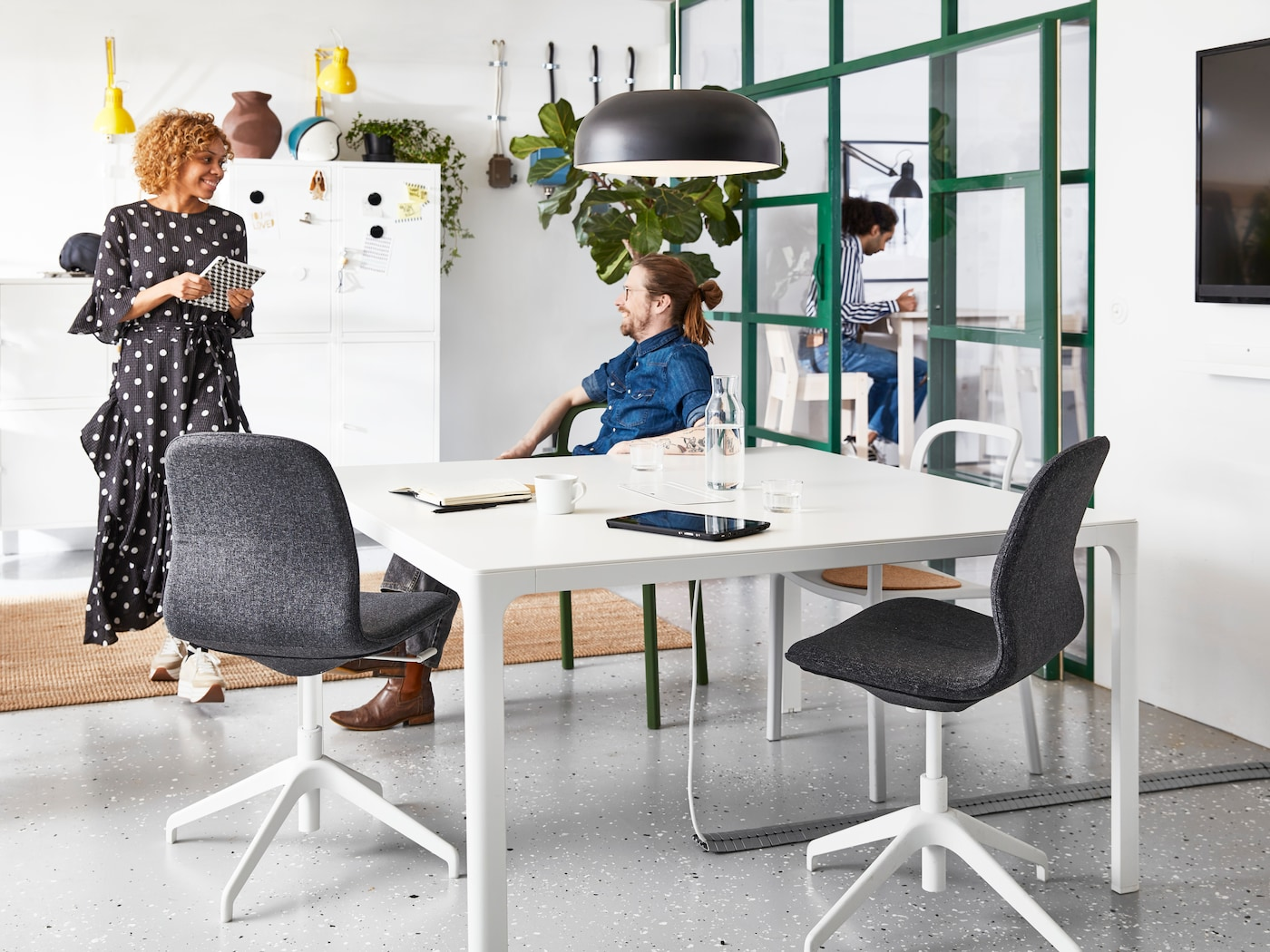 The man sitting on YPPERLIG chair with armrest is talking with a woman holding a notebook in the office where has BAKANT table and LÅNGFJÄLL office swivel chair.