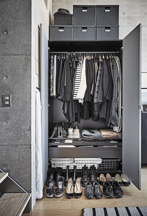 The monochrome contents of an open wardrobe.