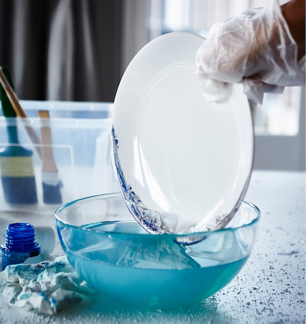 The newly-painted edge of an IKEA FÄRGRIK plate is being dipped into a bowl of water.