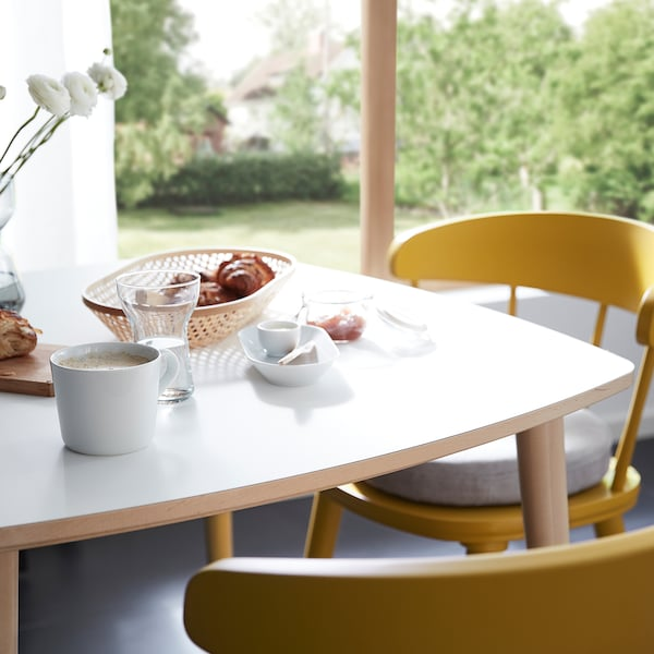 The OMTÄNKSAM table, scratch resistant and easy to clean, is set for breakfast and accompanied by two OMTÄNKSAM chairs.