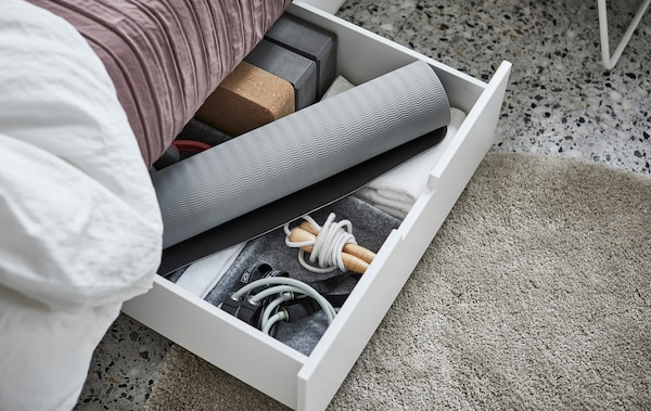 The open drawer of a NORDLI bed filled with yoga mats, jump ropes and other gym equipment.