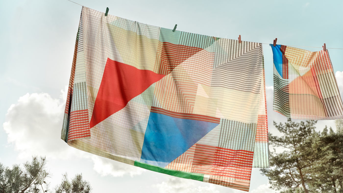 The PIMERNÖT quilt cover and pillowcase is hanging outdoors to dry on a clothes line against the blue summer sky.