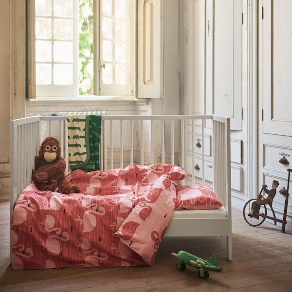 The pink two-sided RÖRANDE quilt cover and pillowcase with a print of cuddling flamingos placed in a child's bed.