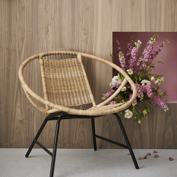 The rattan GAGNET armchair next to some pink flowers.