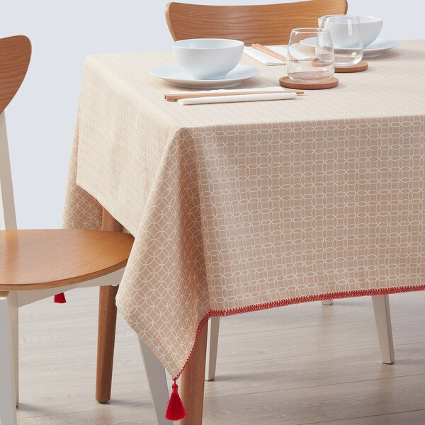 The red patterned SOLGLIMTAR table cloth on a table with two chairs and a table setting.