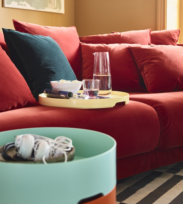 The removable lid of a storage table acts as a tray for snacks and sits on a sofa.