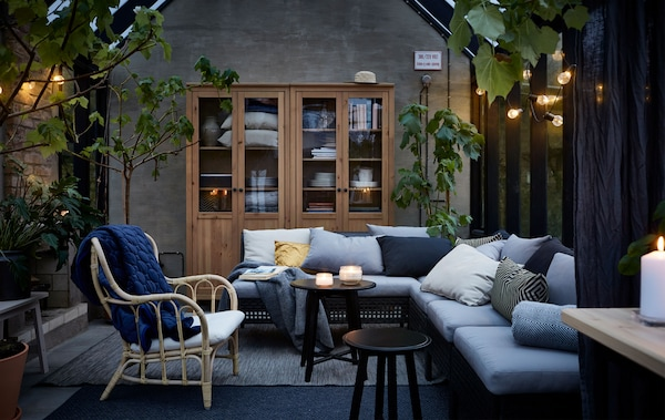The sections in the KUNGSHOLMEN outdoor seating series are combined to create a sofa in a greenhouse turned living room.