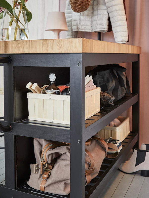 The shelves of an IKEA VADHOLMA kitchen island in black/oak used for storing bags and more inside a hallway.