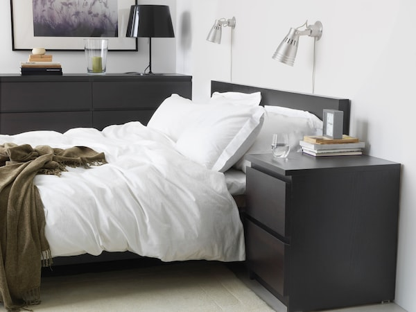 The side of a black-brown bed with white bedding, next to a black brown 2 drawer chest and a dresser behind it.