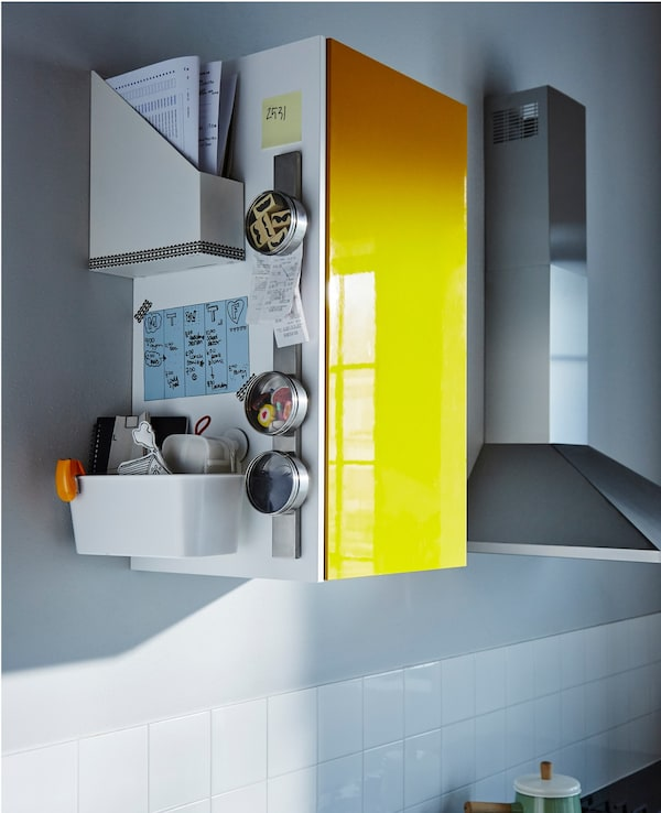 The side of a high kitchen cabinet holds a family schedule, papers and organised odds and ends.