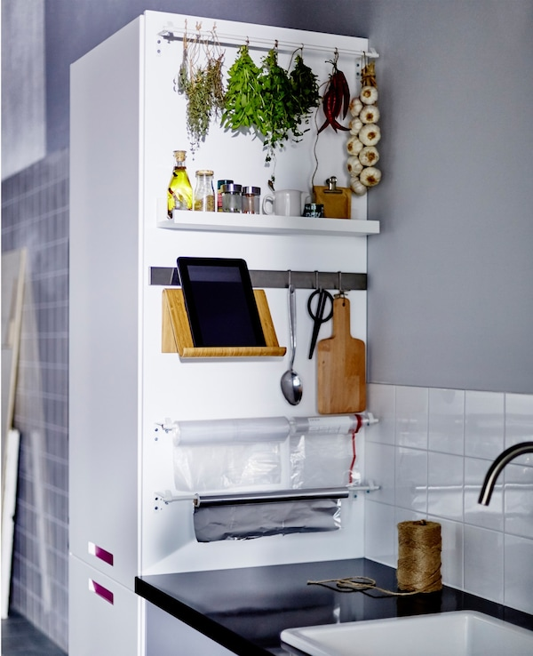 The side of a kitchen cabinet next to a work top stores and organises spices, scissors and a tablet stand.