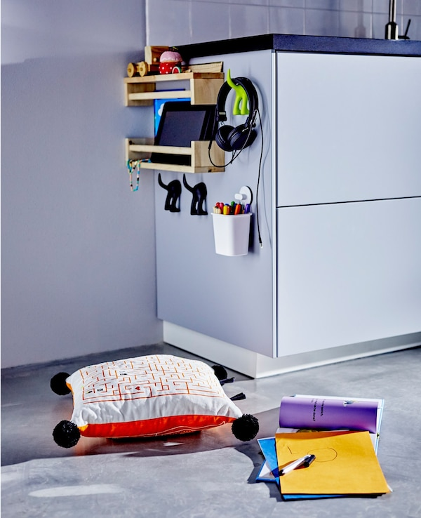 The side of a low kitchen cabinet with shelves and hooks for toy and craft organization for children.