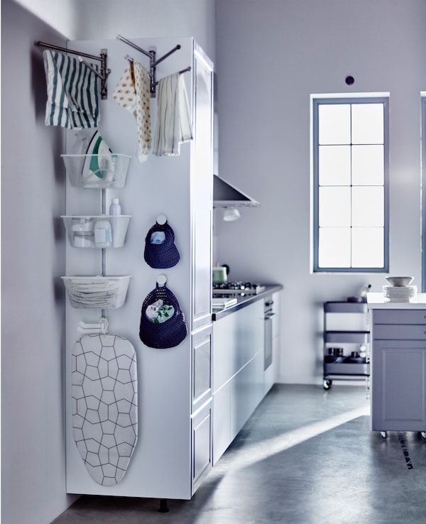 The side of a tall kitchen cabinet with baskets and rails for a laundry station.