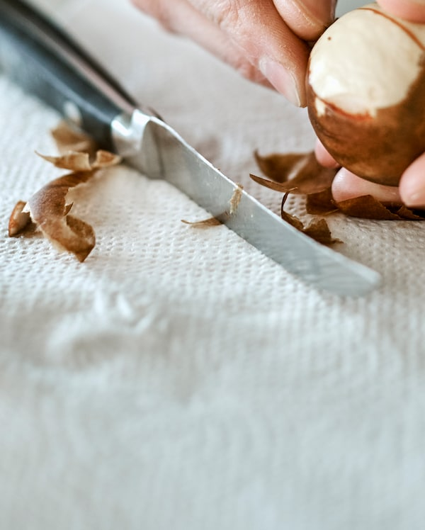 The skin being peeled from an avocado seed with the peel on a paper towel next to a kitchen knife with a black handle.