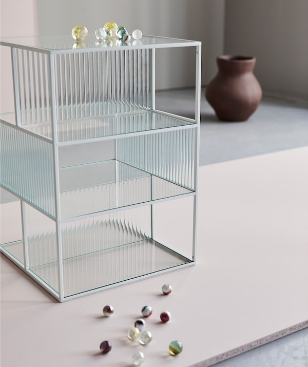 The thin lines and glass panes of a SAMMANHANG display box make a stage for whatever you place in, on or beside it. Here visualised by a handful of glass beads and an INDUSTRIELL vase.