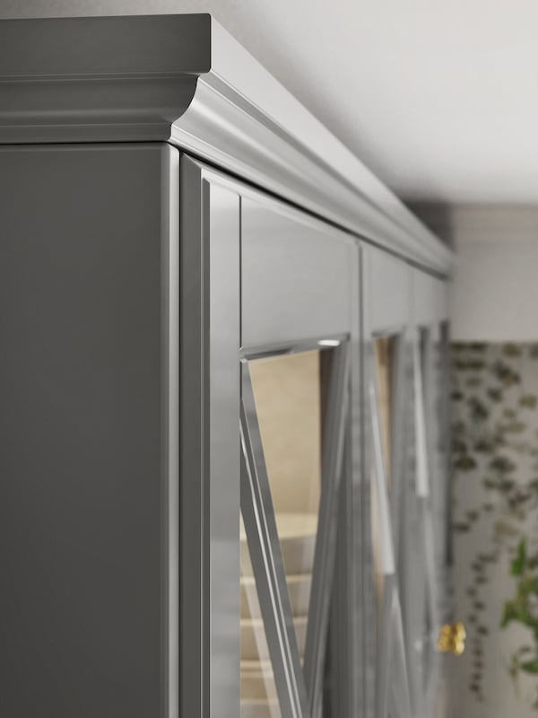 The top corner of a row of grey kitchen cabinets with glass doors and a matching contoured decorative moulding on top.