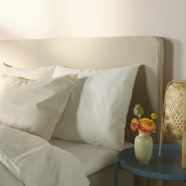 The top of a bed with a headboard, dressed with white bedding and pillows made of sustainable cotton