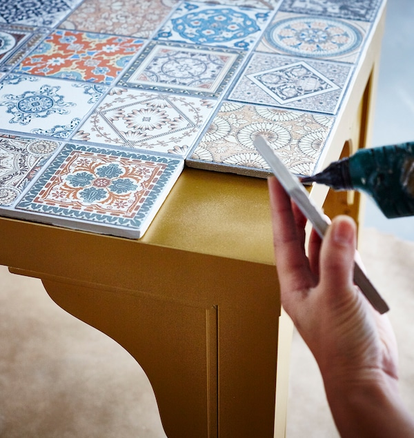 The top of a gold IKEA LACK table is being decorated with a variety of patterned tiles.