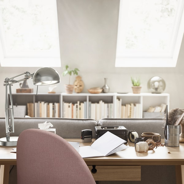 The top of a pink work chair that's in front of a LISABO desk with a work lamp on it and a row of white shelves at the back.