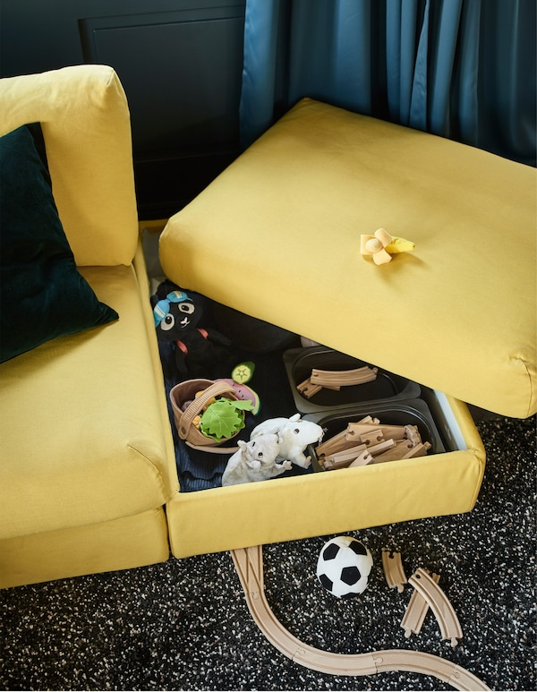 The top of a yellow sofa section is moved to reveal hidden toy storage in the living room.