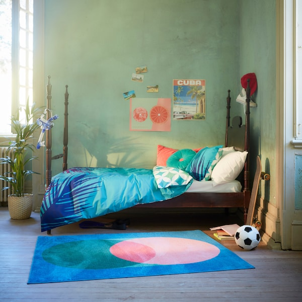 The vibrant GRACIÖS textile series including a quilt cover, cushions and a rug in a bright teenager's bedroom.
