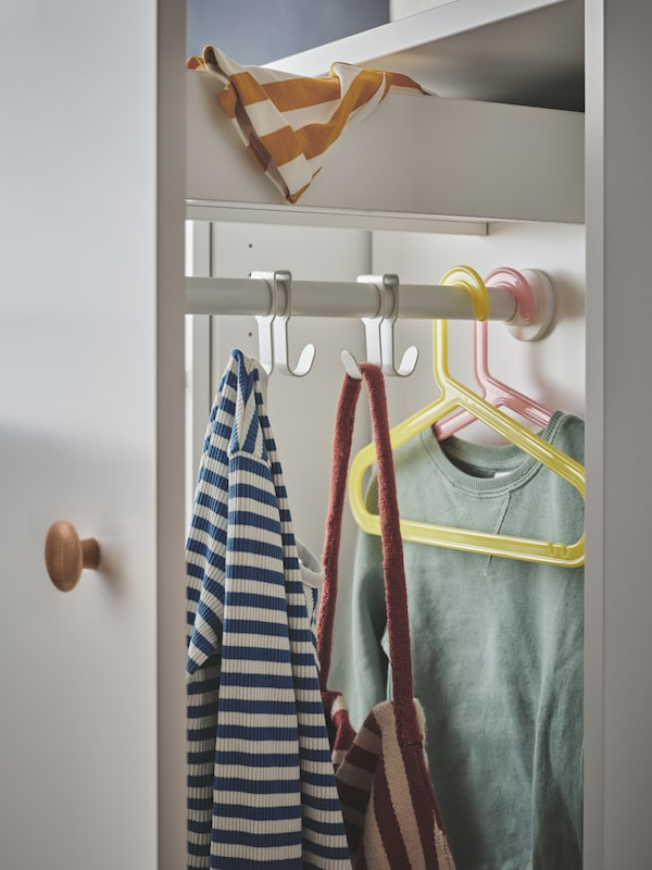 The white SMÅSTAD pull-out storage unit with a top drawer and hooks and hangers holding children's clothes and a bag.