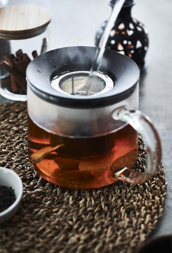 Théière en verre remplie de thé, sur un napperon en osier.
