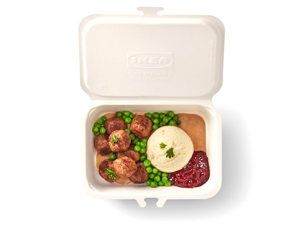 There are meatball, green peas, mashed potato in the to-go box with raspberry and gravy source