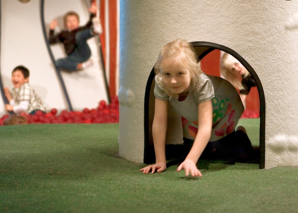 There's a girl crawling out of a tunnel in Småland, and there's a kid staring behind her..