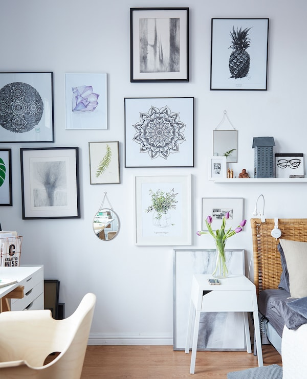 This gallery wall of Margo's artwork blurs the line between bedroom and office.