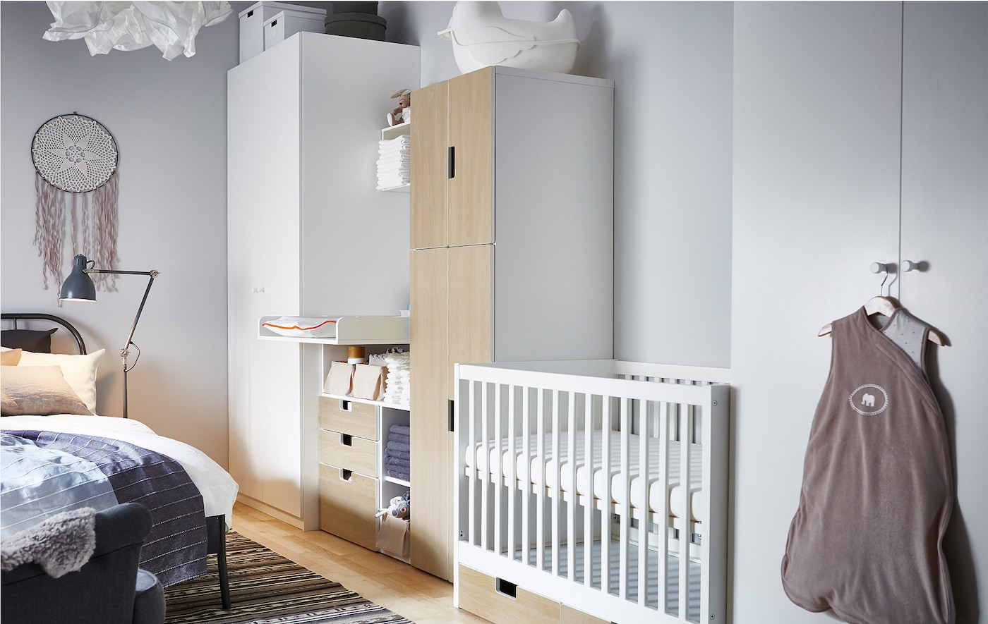 This nursery idea places a cot, changing table and babies storage in between two wardrobes for the parents.
