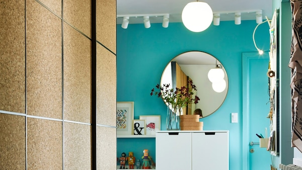 This small hallway has IKEA PAX wardrobe with KIRKENES cork sliding doors for clothes storage. It allows the family to show off their children's creations.